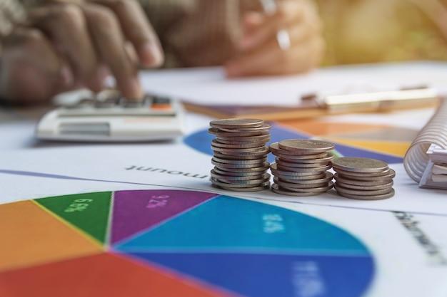 Homme à l'aide de la calculatrice avec des indices financiers boursiers avec pile coin.