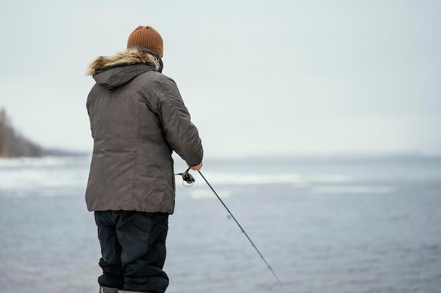 Homme à l'aide d'une canne à pêche