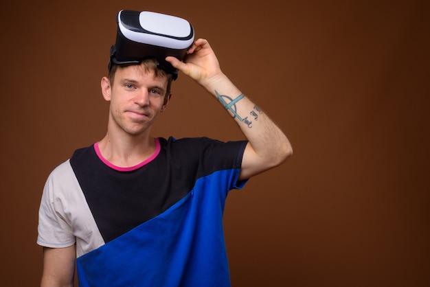 L'homme à l'aide d'un casque de réalité virtuelle contre un mur marron