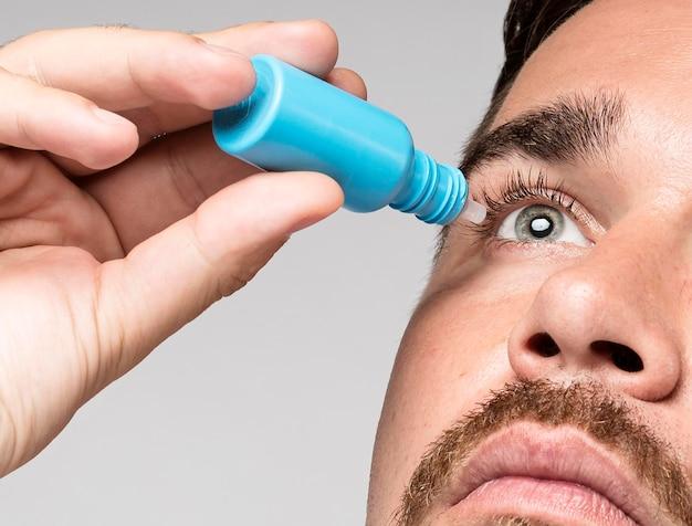 Homme à l'aide de gouttes pour les yeux close-up