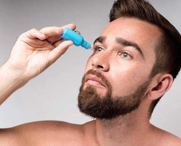 Homme à l'aide de gouttes pour les yeux
