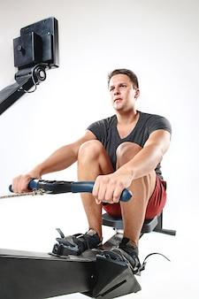 Homme à l'aide d'une machine de presse dans un club de remise en forme.