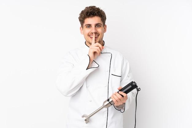 Homme à l'aide d'un mixeur à main isolé sur blanc faisant un geste de silence