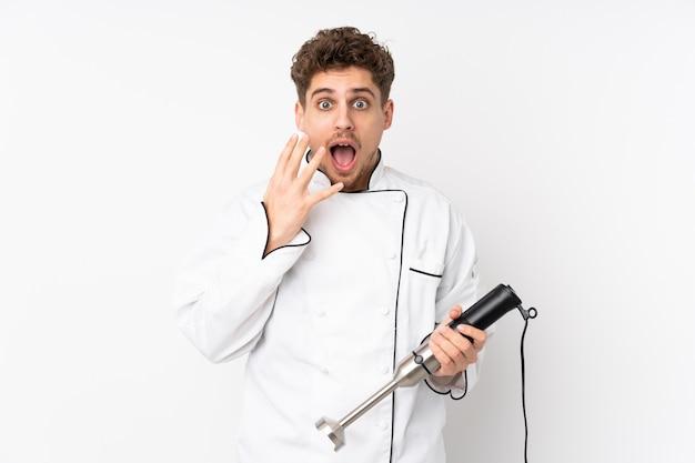Homme à l'aide d'un mixeur plongeant isolé sur blanc avec une expression faciale surprise