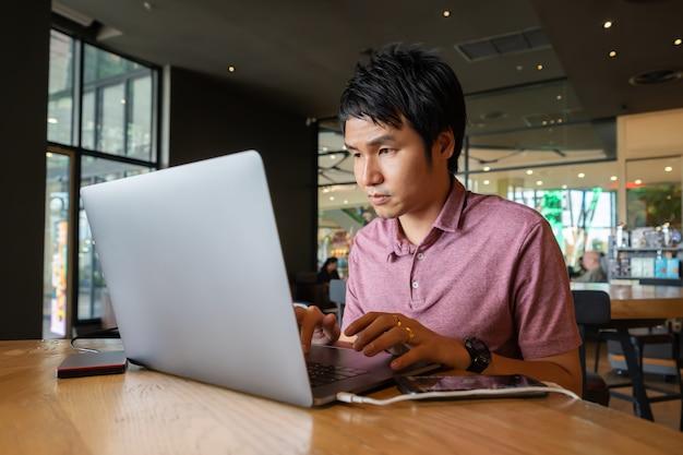 Homme à l'aide d'un ordinateur portable au café