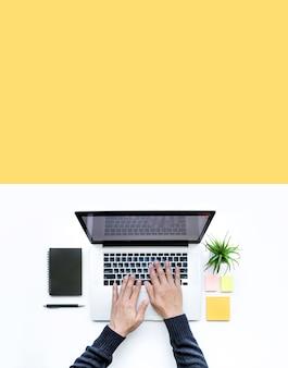 Homme à l'aide d'un ordinateur portable sur table de bureau blanc, mise à plat