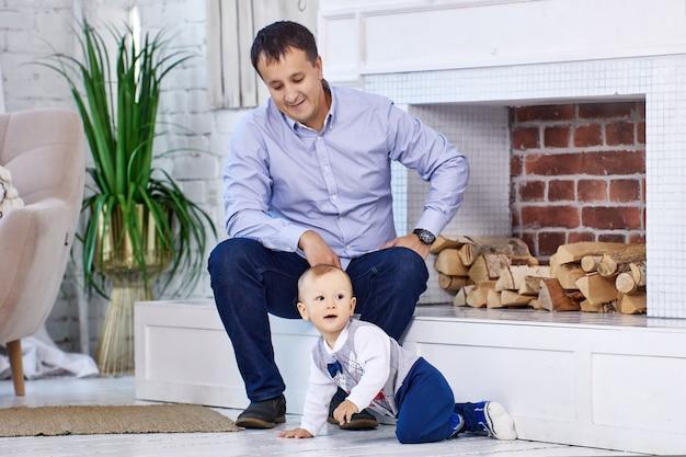 L'homme aide le petit garçon à se tenir debout dans le salon