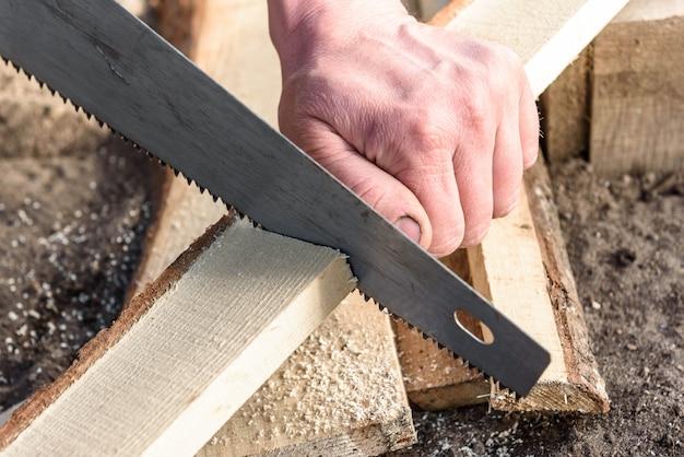 Homme à l'aide d'une scie à main pour couper du bois.
