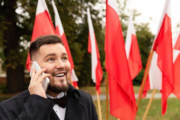 Homme à l'aide de smartphone avec des drapeaux de la pologne derrière