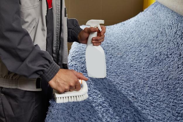L'homme à l'aide de spray chimique pour éliminer les taches de tapis dans le service de nettoyage de tapis