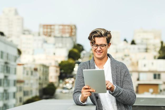 Homme à l'aide d'une tablette numérique sur un toit à san francisco