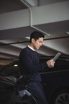 Homme à l'aide de tablette numérique tout en chargeant la voiture électrique
