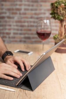 L'homme à l'aide d'une tablette pour travailler, sur une table en bois avec un verre de vin, devant un mur de briques.