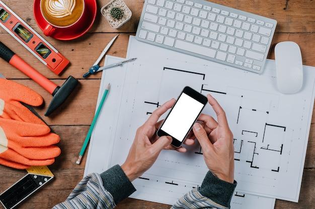 Homme à l'aide de téléphone intelligent avec un écran vide dans les mains touchant sur un écran
