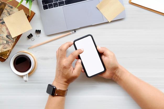 Homme à l'aide de téléphone portable sur la table de bureau en bois blanc avec ordinateur