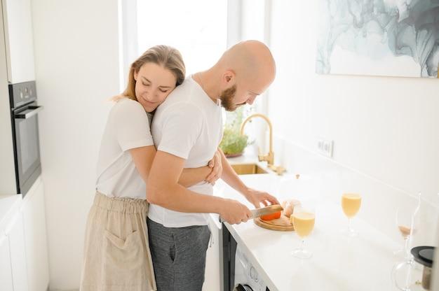 Homme aimant alimentation femme heureuse montrant des soins de cuisson des repas sains ensemble le week-end