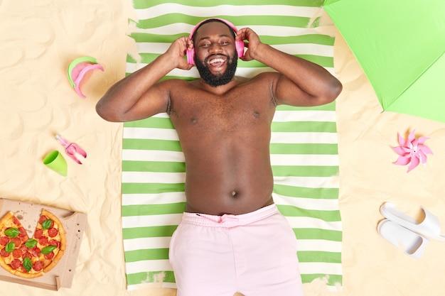 L'homme aime écouter de la musique avec des écouteurs a la peau foncée aime le temps libre à la plage de sable mange une pizza savoureuse a un vrai repos et détente
