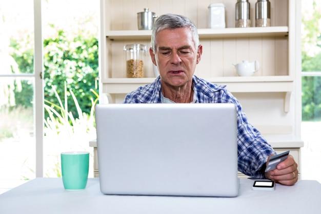 Homme aîné, achats, ligne, portable utilisation