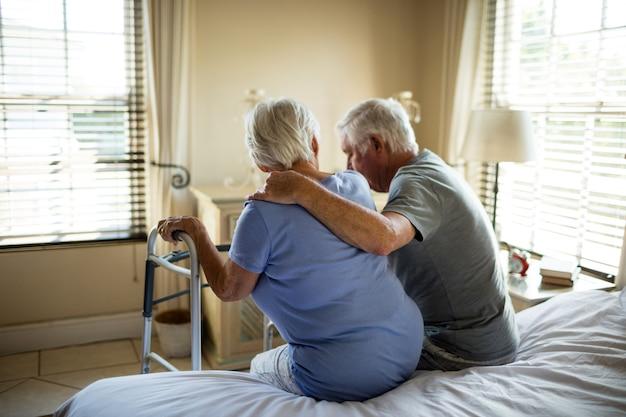 Homme aîné, consoler, femme, dans, chambre à coucher, chez soi