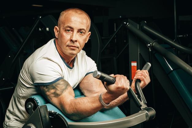 Homme aîné, faire, exercices bras, dans, a, machine entraînement, dans, gymnase