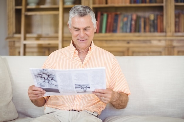 Homme aîné, lecture journal, dans, salle de séjour