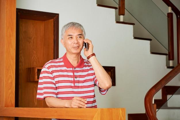 Homme aîné, parler téléphone, dehors