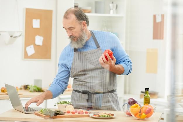 Homme aîné, portable utilisation, pendant, cuisine
