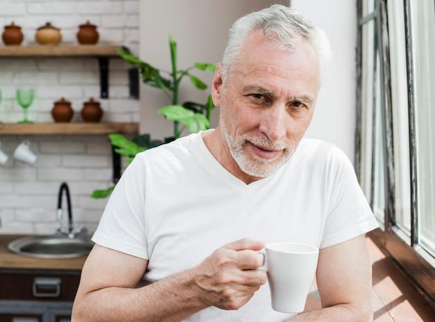 Homme aîné prenant un café