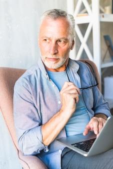 Homme aîné, séance, sur, fauteuil, tenue, lunettes, utilisation, ordinateur portable