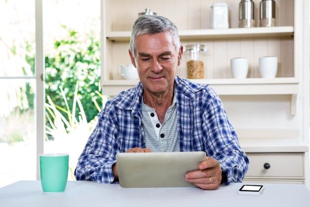 Homme aîné, utilisation, tablette numérique, contre, étagères
