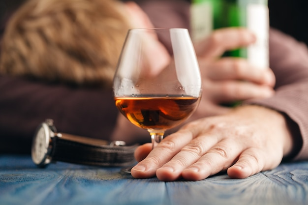 Homme alcoolique dormir après avoir bu plus de whisky