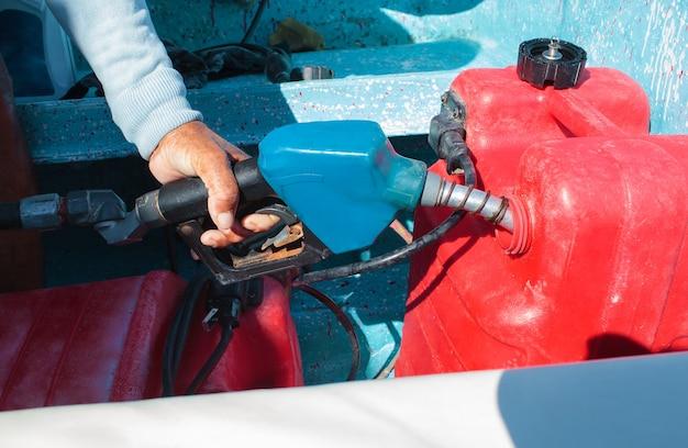 Homme alimentant le réservoir d'un bateau à moteur avant le voyage