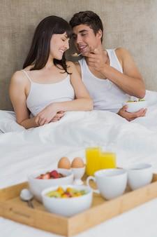 Homme, alimentation, céréales petit déjeuner, à, femme, dans, chambre à coucher