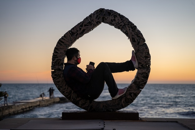 Homme allongé en attente de prendre une photo du coucher de soleil au bord de la mer à palma de majorque, espagne
