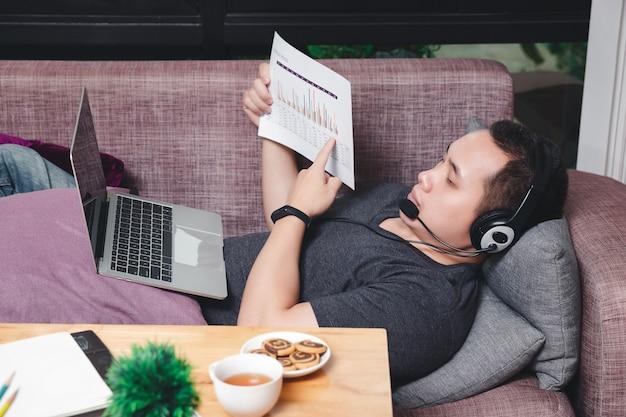 Homme allongé sur le canapé et appel vidéo avec des collègues