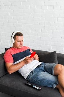 Homme allongé sur le canapé en écoutant de la musique sur le casque