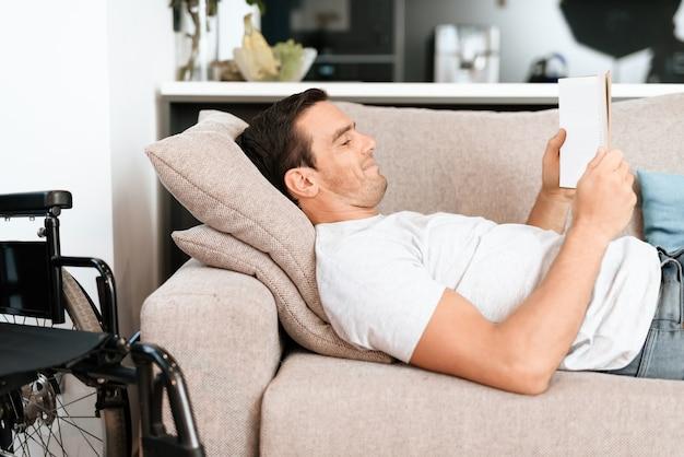 Homme allongé sur un canapé avec tablette près de fauteuil roulant