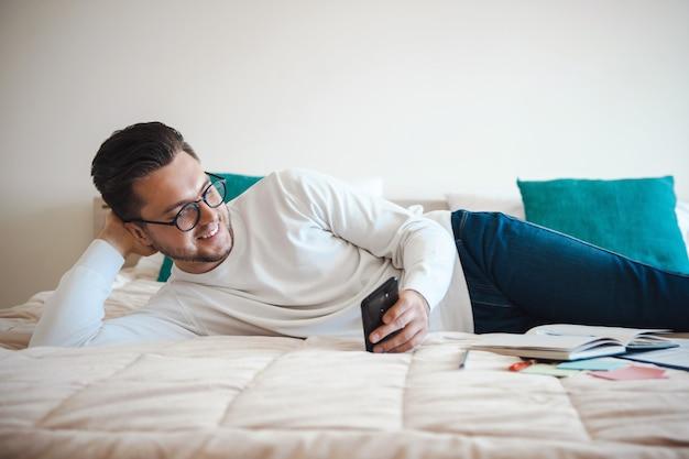 Homme allongé d'un côté sur le lit avec une main sous la tête et avec l'autre écrit des messages