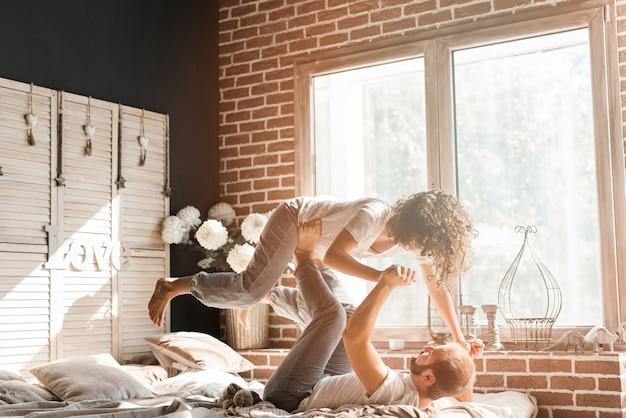 Homme allongé sur le lit, portant sa femme sur ses pieds près de la fenêtre