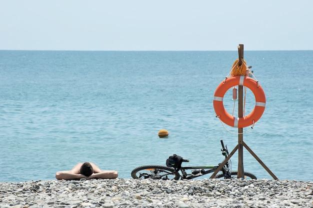 Un homme allongé sur la plage de galets à côté de la bouée de sauvetage et du vélo