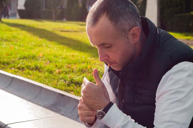 Un homme allume une cigarette à l'extérieur. le point focal est sur la cigarette. un bel homme qui allume la cigarette sur la rue citadine. la mode de la ville.