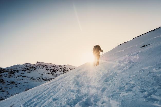 Homme alpiniste escalade à la montagne en hiver au coucher du soleil