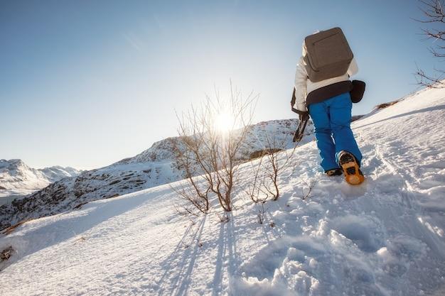 Homme d'alpiniste s'élevant à la montagne de crête en hiver au coucher du soleil brillant
