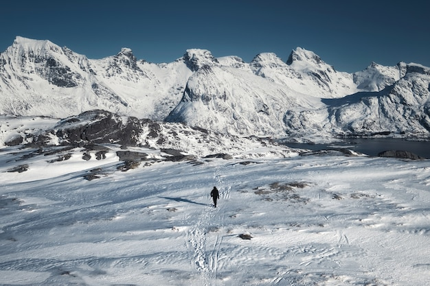 Homme alpiniste trekking sur la colline de neige avec chaîne de montagnes à l'île de senja, norvège