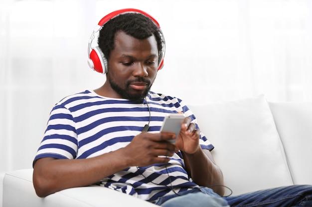 Homme américain africain, à, écouteurs, sur, sofa, dans, salle