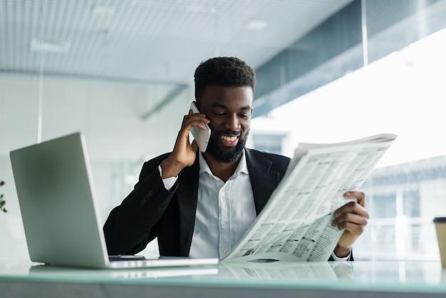 Homme américain africain, lecture journal, et, parler téléphone, dans, bureau