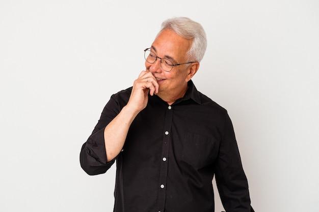 Homme américain senior isolé sur fond blanc détendu en pensant à quelque chose en regardant un espace de copie.