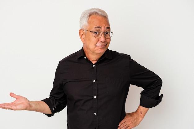 Homme américain senior isolé sur fond blanc montrant un espace de copie sur une paume et tenant une autre main sur la taille.