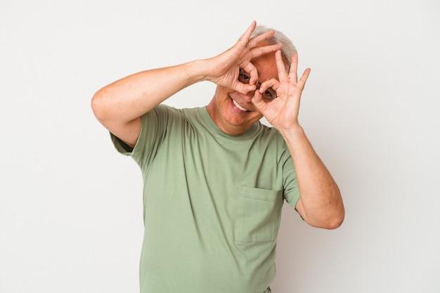 Homme américain senior isolé sur fond blanc montrant un signe d'accord sur les yeux