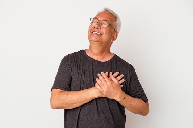 Homme américain senior isolé sur fond blanc en riant en gardant les mains sur le cœur, concept de bonheur.